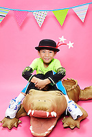 Asian boy wearing a black hat with white stars sitting on a plush aligator against pink seamless<br /> Photographed at the Photoville Photo Booth September 20, 2015