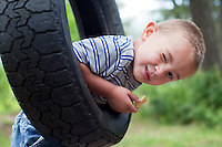 Young boy winking at camera on tyre swing