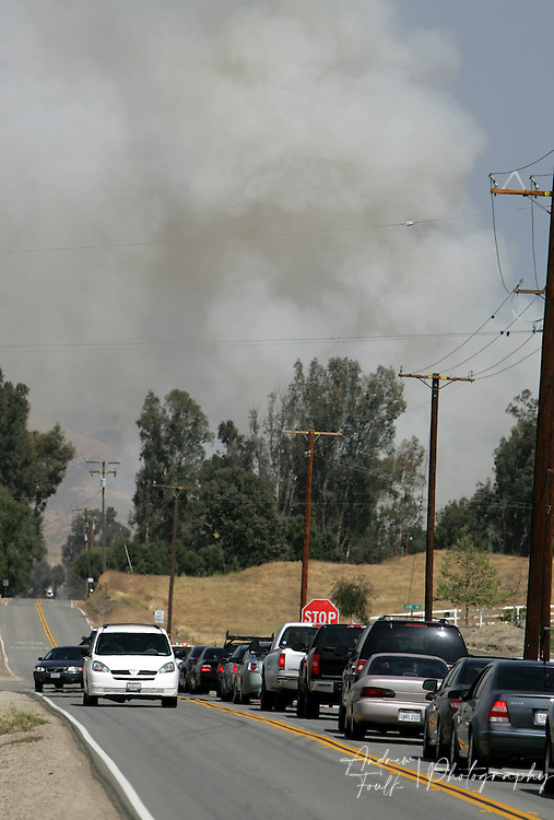 /Andrew Foulk/ For the Californian/.Motorist are stopped from proceeding East on Scott Road due a CHP road block as a plume of smoke raises in the distance from a fire that started at around 2pm in the area just North of Keller Road and South of Scott Road. The Fire consumed an estimated 200 acres and caused the closure of Scott, and Winchester Roads.