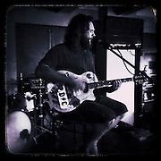 Sean Degan playing guitar in a pub,