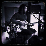 Sean Degan playing guitar in a pub,