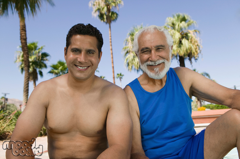 Senior Father and Son by Swimming Pool