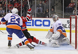 Mar 8; Newark, NJ, USA; New York Islanders defenseman Steve Staios (24) trips New Jersey Devils left wing Ilya Kovalchuk (17) while New York Islanders goalie Evgeni Nabokov (20) makes a save during the second period at the Prudential Center.