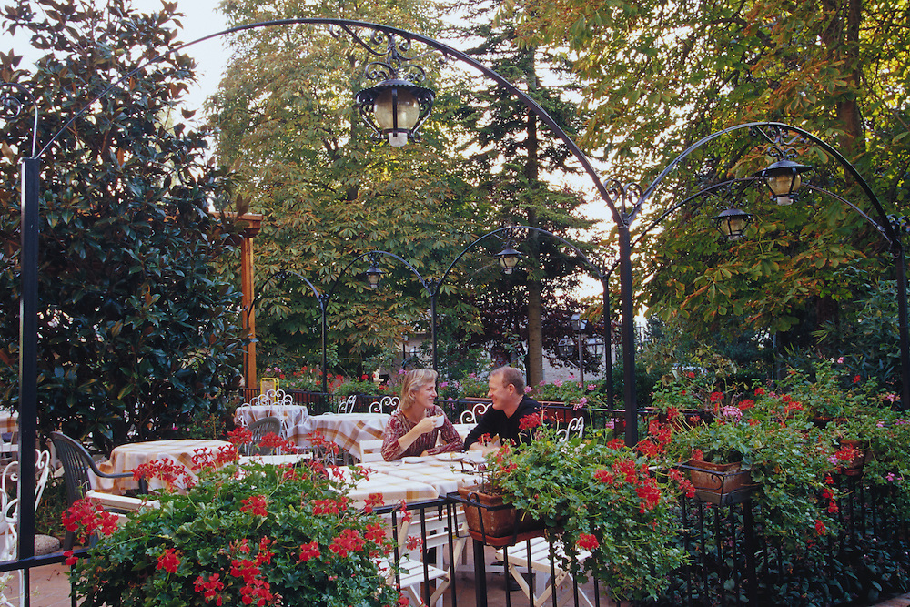 Europe, Italy, Tuscany, couple having coffee in garden at monastery