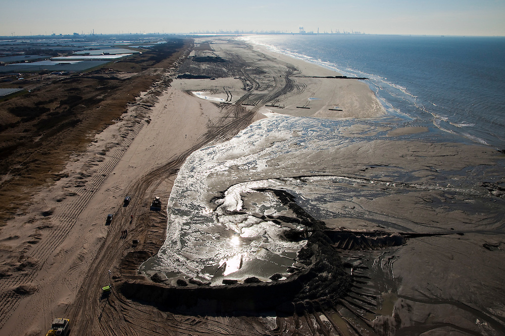 Nederland, Zuid-Holland, Monster, 18-03-2009; Versterking van de kust van Delfland tussen Ter Heijde en 's-Gravenzande door middel van zandsuppletie. Om het zand dat hoog op het strand opgespoten wordt vast te houden, zijn er dammen van zand aangelegd. De Delflandse kust is een van de 'zwakke schakels'. Maasvlakte en ingang nieuwe Waterweg aan de horizon. .Strengthening of the coast of Delfland between Hoek van Holland and The Hague by means of sand-supplementation. Bulldozers have made dams to keep the new sand in place when it is sprayed high on the beach. Maasvlakte entrance Port of Rotterdam / Nieuwe Waterweg at the horizon..Swart collectie, luchtfoto (toeslag); Swart Collection, aerial photo (additional fee required); .foto Siebe Swart / photo Siebe Swart