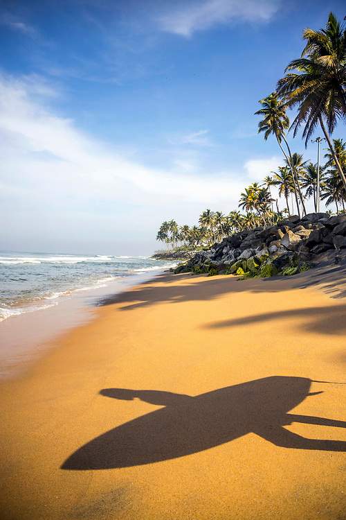 VARKALA, INDIA - 28th September 2019 - Creative stock image of a silhouette shadow from a surfer carrying a surfboard into the sea on a sandy beach while surfing during an early morning sunrise at Varkala Cliff Beach, Kerala, Southern India