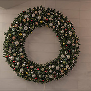 Large Christmas Wreath with decorations on wall in underground passageway to Brookfield Place.