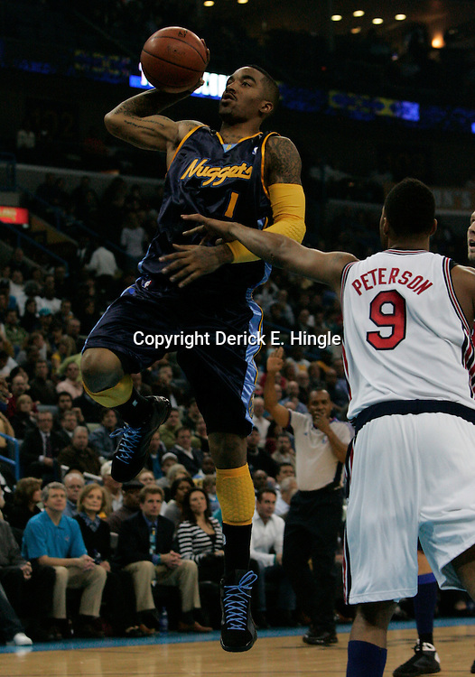 28 January 2009:  Denver Nuggets guard J.R. Smith (1) shoots over New Orleans Hornets guard Morris Peterson (9) during a 94-81 win by the New Orleans Hornets over the Denver Nuggets at the New Orleans Arena in New Orleans, LA. The Hornets wore special throwback uniforms of the former ABA franchise the New Orleans Buccaneers for the game as they honored the Bucs franchise as a part of the NBA's Hardwood Classics series. .