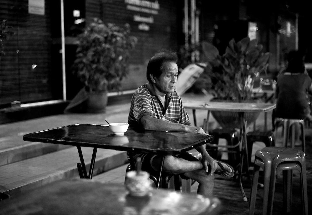 Ein Mann hat gerade sein Abendessen in einem Straßenrestaurant in Pattaya, Thailand beendet