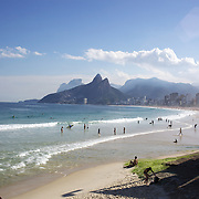 A beach scene looking along the stretch of beaches including Arpoador, Ipanema and Leblon beaches, from Pedra do Arpoador showing the twin peaks of dois irmaos in the distance. Rio de Janeiro, Brazil. 3rd July 2010. Photo Tim Clayton....