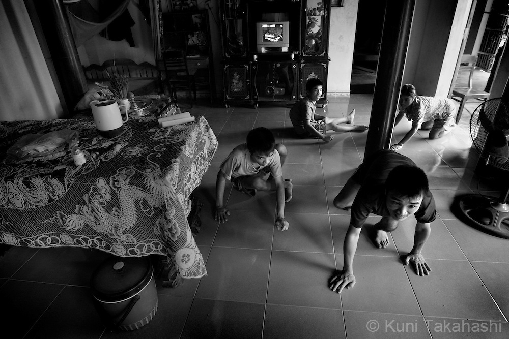 Four children of Tran Van Tram, 60, crawl on the floor at their house in Quang Tri Province in northern Vietnam on June 25, 2009. .Tram, who lived in Cam Lo, one of the most heavily sprayed areas during the war, has seven children and four of them have severe developmental disabilities.....