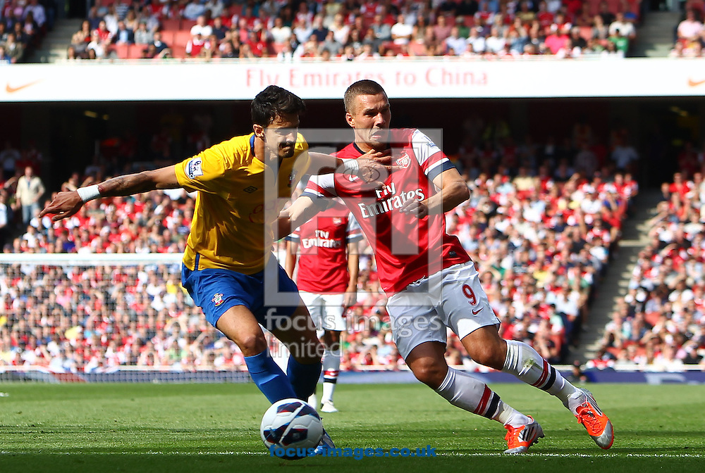 Picture by John  Rainford/Focus Images Ltd +44 7506 538356.15/09/2012.Lukas Podolski of Arsenal and Jose Fonte of Southampton during the Barclays Premier League match at the Emirates Stadium, London.