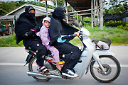 "Sept. 27, 2009 -- BACHO, THAILAND: Muslim Thai families use motorcycles for family transportation in Bacho, Narathiwat, Thailand. Thailand's three southern most provinces; Yala, Pattani and Narathiwat are often called ""restive"" and a decades long Muslim insurgency has gained traction recently. Nearly 4,000 people have been killed since 2004. The three southern provinces are under emergency control and there are more than 60,000 Thai military, police and paramilitary militia forces trying to keep the peace battling insurgents who favor car bombs and assassination.   Photo by Jack Kurtz"