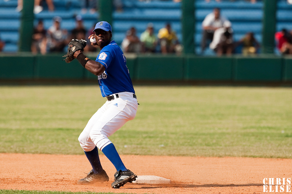 15 February 2009: Second base Rudy Reyes of the Occidentales throws the ball to first base during a training game of Cuba Baseball Team for the World Baseball Classic 2009. The national team is pitted against itself, divided in two teams called the Occidentales and the Orientales. The Orientales win 12-8, at the Latinoamericano stadium, in la Habana, Cuba.