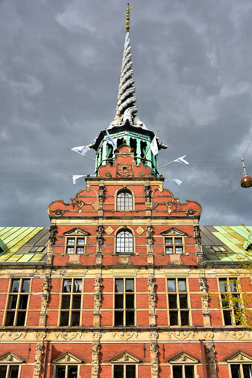 Dragon Spire on B&oslash;rsen in Copenhagen, Denmark <br /> Take a close look at the tower on the B&oslash;rsen or Old Stock Exchange. The intertwining dragons on the 197 foot spire represent the Kalmar Union. This was a close relationship among the Nordic countries of Denmark, Norway and Sweden. The tower was finished in 1625 and replaced in 1775.  According to legend, it has protected the building from multiple fires that destroyed its neighbors on Slotsholmen over the centuries.