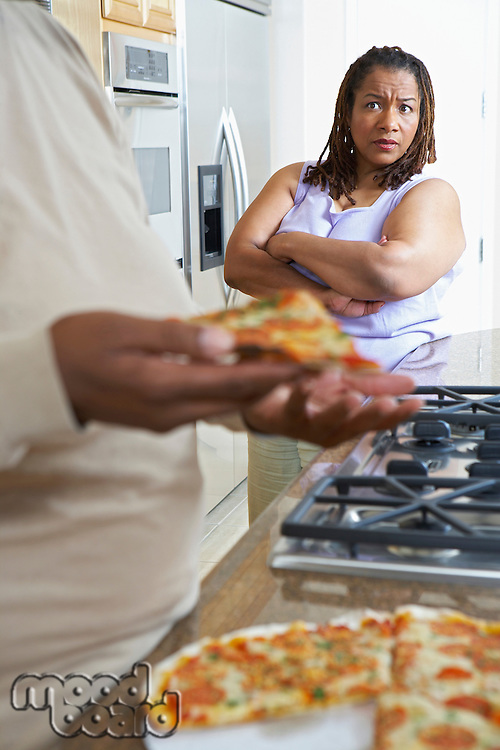 Woman watching man taking slice of pizza from kitchen counter