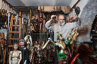 "PALERMO - 26 DECEMBER 2015: Mimmo Cuticchio, a ""puppeteer"", tries out a ""pupo"" (puppet) for an upcoming performance in the ""Teatro dei Pupi di Mimmo Cuticchio"" (Mimmo Cuticchio's puppet theatre) in Palermo, Italy, on December 26th 2015.<br /> <br /> Mimmo Cuticchio is the direct heir of an age-old form of popular (street) theatre, the Teatro dell'Opera dei pupi siciliani, Sicilian Puppet Theatre, handed down to him by his father Giacomo. It is to Mimmo that we owe the relaunch of this type of theatre, which after the decline it experienced in the fifties and sixties, had become relegated mostly to the realm of folklore.<br /> <br /> In 1973 Cuticchio opened the Teatro dei Pupi Santa Rosalia in Palermo, and in 1977 he founded the Associazione Figli d'Arte Cuticchio, with the intention of safeguarding and handing down the artistic tradition of the Opera dei Pupi. In 2015 his collection of Sicilian Pupi which includes 19th and 20th Century marionettes, was purchased by the Fondazione Sicilia, and is now on show at the Palazzo Branciforte in Palermo. In 2001 UNESCO entered the Opera dei Pupi in the list of Proclaimed Masterpieces, and in 2008 it inscribed it on the Representative List of the Intangible Cultural Heritage of Humanity.<br /> <br /> <br /> PALERMO - 26 DICEMBRE 2015: Il puparo Mimmo Cuticchio prova un puparo dietro le quinte del suo teatro dei pupi in via Bara all'Olivella a Palermo, il 26 dicembre 2015.<br /> <br /> Mimmo Cuticchio è un importante erede della tradizione dei cuntisti siciliani e dell'Opera dei Pupi, oggi iscritta tra i Patrimoni orali e immateriali dell'umanità dell'UNESCO. Figlio del noto puparo Giacomo Cuticchio, nel 1973 apre a Palermo il Teatro dei Pupi Santa Rosalia. Nel 1977 fonda l'Associazione figli d'Arte Cuticchio, che si prefigge di salvaguardare l'arte dell'Opera dei Pupi."