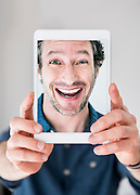 Playful mid adult man making faces while photographing self through digital tablet