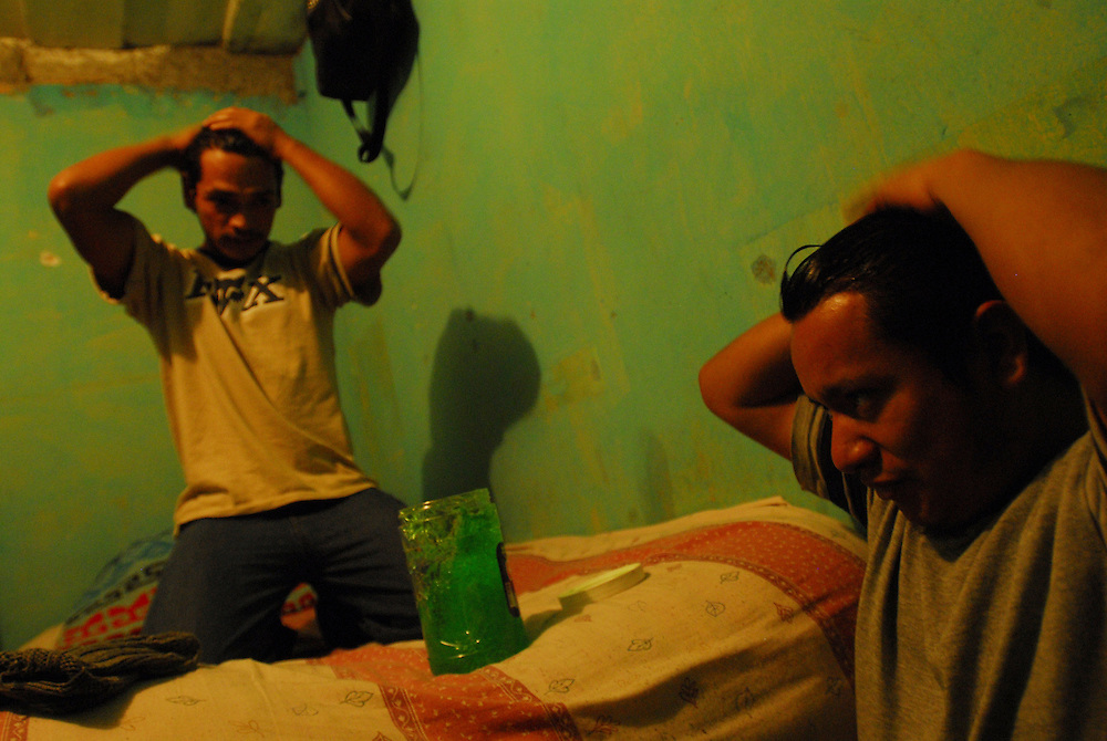"""Heber Bersario Acevedo, 25, left, styles his hair with gel at Casa Hogar, a rehabilitation home for alcohol and drug addicts, outside of Antigua, Guatemala. Acevedo has been living at Casa Hogar for one month and was heavily smoking crack and marijuana """"for years"""" when he decided to seek treatment for his addiction...Casa Hogar currently houses 44 men (with a maximum of 60.) Jorge Rosales, himself a former drug user, founded the home 2 years ago after he kicked his habit and left the garbage dump he had been living in for thirteen months...If accepted into Casa Hogar the voluntary residents must first spend 6 days in a first floor room of mattresses, are denied showers and must eat meals separately from other residents. Patients in the first floor zone suffer from convulsions, vomiting and other withdrawal symptoms and are monitored round the clock by a nurse. Most alcoholics who enter the program have been drinking rubbing alcohol, according to Rosales, because it is so inexpensive...""""If they make it"""" says resident Byron Rosales, """"they can join us up top."""" It is up to the individual when they feel they are ready to leave the home."""