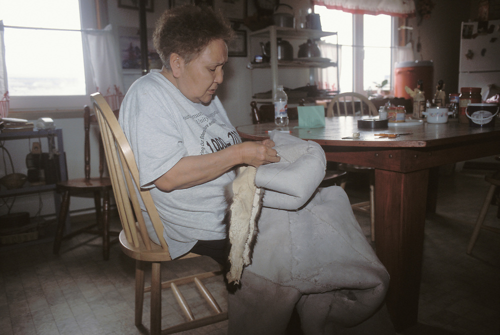 Barrow, Alaska. A native woman sews together a parka from seal skin in her Barrow home Kitchen.