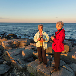 Two women birdwatching at Seapoint Beach in Kittery, Maine.