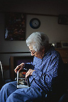 ca. May 1999 --- Elderly Woman Looking at Family Photographs --- Image by © Owen Franken/CORBIS