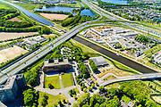 Nederland, Noord-Brabant, Den Bosch, 13-05-2019; Knooppunt Hintham, half-sterknooppunt. Het knooppunt is onderdeel van de Ring 's-Hertogenbosch en verbindt rijksweg A59 (in oostelijke richting, naar links) met rijksweg A2 (Noord-Zuid). Maximakanaal, in het hart van het knooppunt Heijmans Materieel Beheer, links hoofdkantoot van Heijmans.<br /> Hintham junction, near Den Bosch.<br /> <br /> aerial photo (additional fee required); luchtfoto (toeslag op standard tarieven); copyright foto/photo Siebe Swart