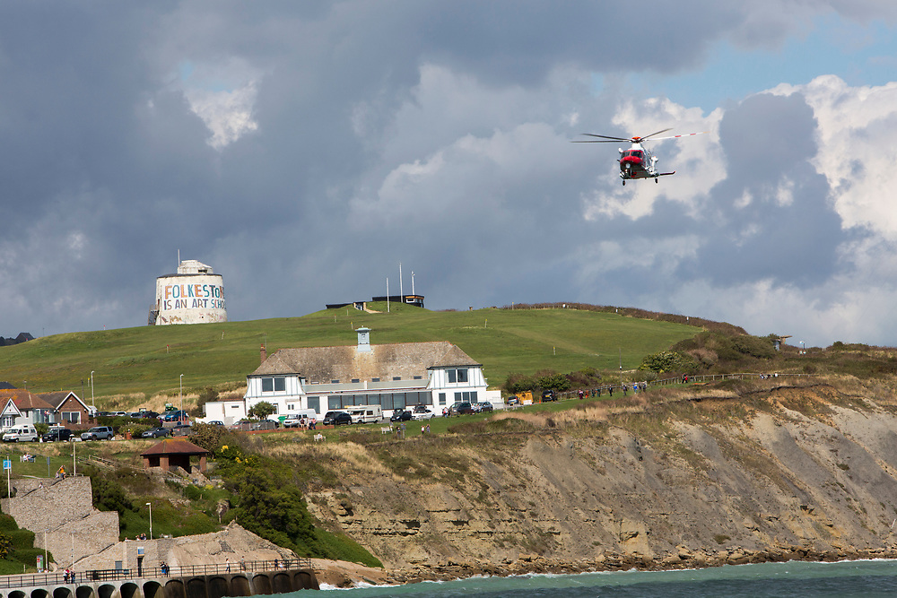 The HM Coastguard rescue helicopter (G-C1JW)  flying over the Folkestone is an Art School banner, attached to Folkestone's most prominent Martello Tower on the east cliff. The banner has been designed by the artist Bob and Roberta Smith as part of the 2017 Folkestone Triennial. Folkestone, Kent.(photo by Andrew Aitchison / In pictures via Getty Images)