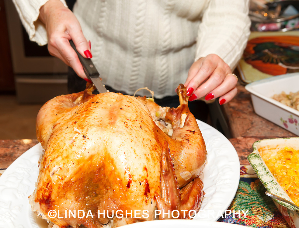 Woman carving turkey at Thanksgiving