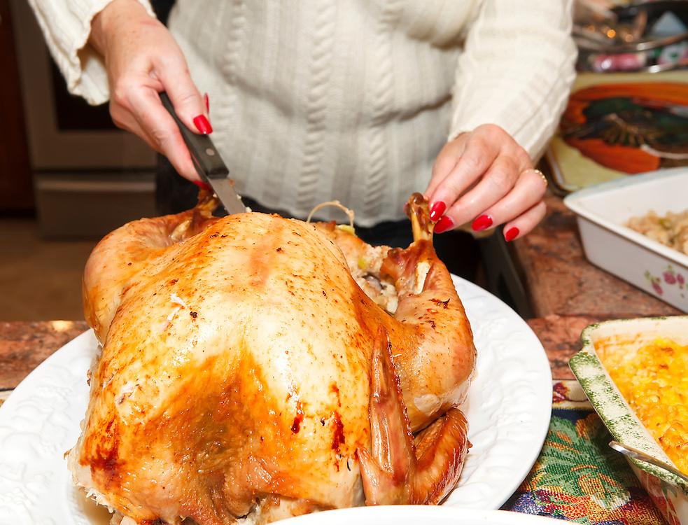 Woman carving turkey at Thanksgiving
