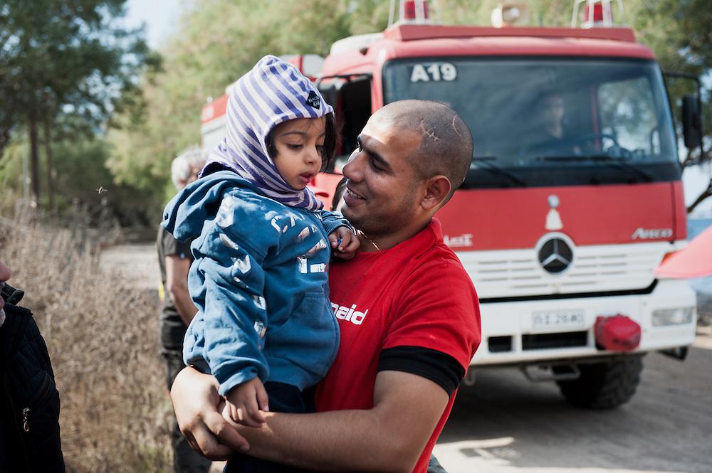 ActionAid's translator Moustafa holds Shiraz from Deir ez-Zor Syria at Skala Sykamias, Lesvos, Greece.