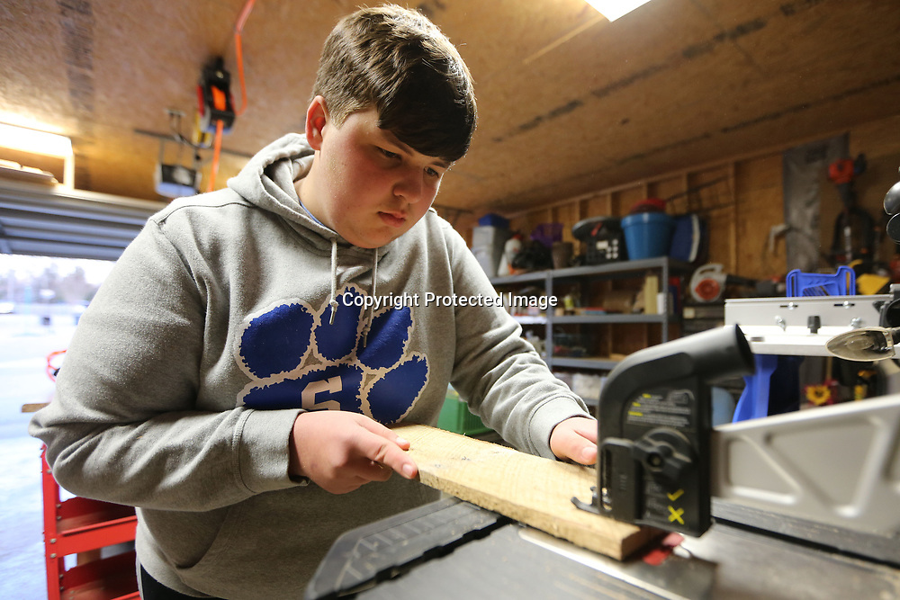 After marking off his pattern for the birdhouse floor, Bryce uses his new Blade Runner, or jig saw table to make his cuts.