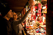 Customers shopping for Christmas ornaments at Christmas market, Winter Wonderland, in Hyde Park, London
