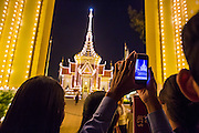 "30 JANUARY 2013 - PHNOM PENH, CAMBODIA:    People use their smart phones to photograph the crematorium for late Cambodian King Norodom Sihanouk in Phnom Penh. Sihanouk (31 October 1922 - 15 October 2012) was the King of Cambodia from 1941 to 1955 and again from 1993 to 2004. He was the effective ruler of Cambodia from 1953 to 1970. After his second abdication in 2004, he was given the honorific of ""The King-Father of Cambodia."" Sihanouk held so many positions since 1941 that the Guinness Book of World Records identifies him as the politician who has served the world's greatest variety of political offices. These included two terms as king, two as sovereign prince, one as president, two as prime minister, as well as numerous positions as leader of various governments-in-exile. He served as puppet head of state for the Khmer Rouge government in 1975-1976. Most of these positions were only honorific, including the last position as constitutional king of Cambodia. Sihanouk's actual period of effective rule over Cambodia was from 9 November 1953, when Cambodia gained its independence from France, until 18 March 1970, when General Lon Nol and the National Assembly deposed him. Upon his final abdication, the Cambodian throne council appointed Norodom Sihamoni, one of Sihanouk's sons, as the new king. Sihanouk died in Beijing, China, where he was receiving medical care, on Oct. 15, 2012. His cremation is scheduled to take place on Feb. 4, 2013. Over a million people are expected to attend the service.        PHOTO BY JACK KURTZ"
