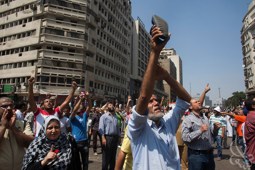 "Supporters of deposed Egyptian President Mohamed Morsi wave shoes and hurl insults as a military helicopter flies overhead during intense street clashes during the August 16, 2014 ""Day of Rage"" protests in Cairo, Egypt."