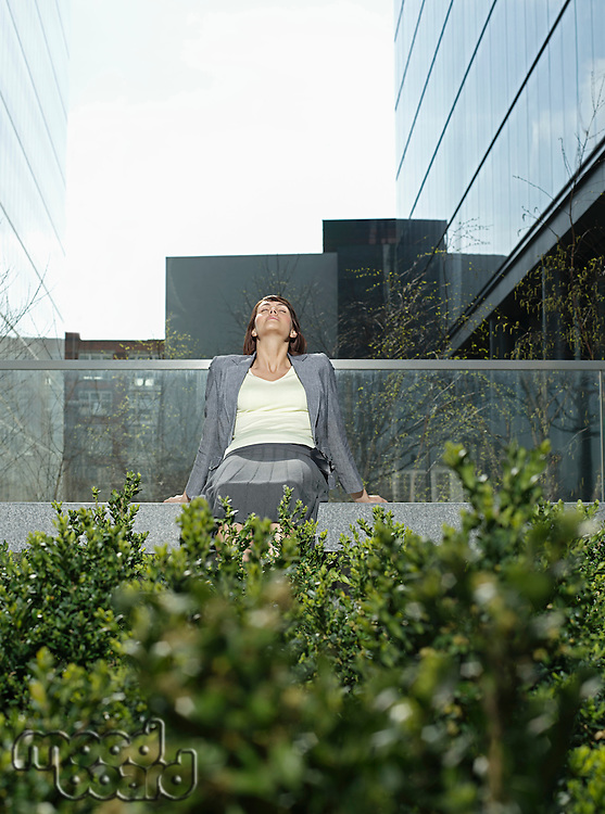 Mid adult businesswoman relaxing on wall outside office buildings