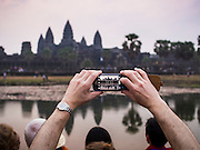"14 MARCH 2105 - SIEM REAP, SIEM REAP, CAMBODIA: A tourist photographs Angkor Wat with his smart phone at sunrise. The area known as ""Angkor Wat"" is a sprawling collection of archeological ruins and temples. The area was developed by ancient Khmer (Cambodian) Kings starting as early as 1150 CE and renovated and expanded around 1180CE by Jayavarman VII. Angkor Wat is now considered the seventh wonder of the world and is Cambodia's most important tourist attraction.   PHOTO BY JACK KURTZ"