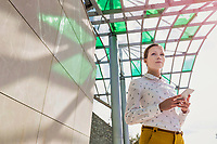 Low angle view of young attractive businesswoman standing while using smartphone
