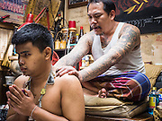 "27 MAY 2015 - BANGKOK, THAILAND: AJARN NENG ONNUT blesses the tattoos of blind man who came to have his tattoos blessed on his birthday. Ajarn Neng is a revered master of sacred tattoos and sees people all day at his Bangkok home. Sak Yant (Thai for ""tattoos of mystical drawings"" sak=tattoo, yantra=mystical drawing) tattoos are popular throughout Thailand, Cambodia, Laos and Myanmar. The tattoos are believed to impart magical powers to the people who have them. People get the tattoos to address specific needs. For example, a business person would get a tattoo to make his business successful, and a soldier would get a tattoo to help him in battle. The tattoos are blessed by monks or people who have magical powers. Ajarn Neng, a revered tattoo master in Bangkok, uses stainless steel needles to tattoo, other tattoo masters use bamboo needles. The tattoos are growing in popularity with tourists, but Thai religious leaders try to discourage tattoo masters from giving tourists tattoos for ornamental reasons.     PHOTO BY JACK KURTZ"