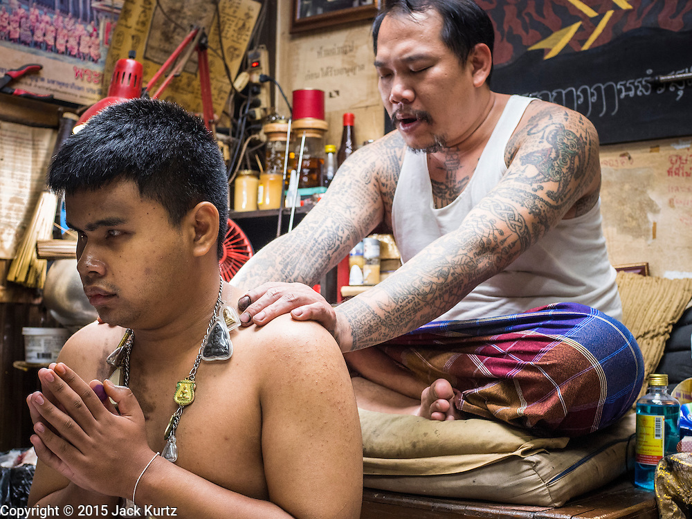 """27 MAY 2015 - BANGKOK, THAILAND: AJARN NENG ONNUT blesses the tattoos of blind man who came to have his tattoos blessed on his birthday. Ajarn Neng is a revered master of sacred tattoos and sees people all day at his Bangkok home. Sak Yant (Thai for """"tattoos of mystical drawings"""" sak=tattoo, yantra=mystical drawing) tattoos are popular throughout Thailand, Cambodia, Laos and Myanmar. The tattoos are believed to impart magical powers to the people who have them. People get the tattoos to address specific needs. For example, a business person would get a tattoo to make his business successful, and a soldier would get a tattoo to help him in battle. The tattoos are blessed by monks or people who have magical powers. Ajarn Neng, a revered tattoo master in Bangkok, uses stainless steel needles to tattoo, other tattoo masters use bamboo needles. The tattoos are growing in popularity with tourists, but Thai religious leaders try to discourage tattoo masters from giving tourists tattoos for ornamental reasons.     PHOTO BY JACK KURTZ"""