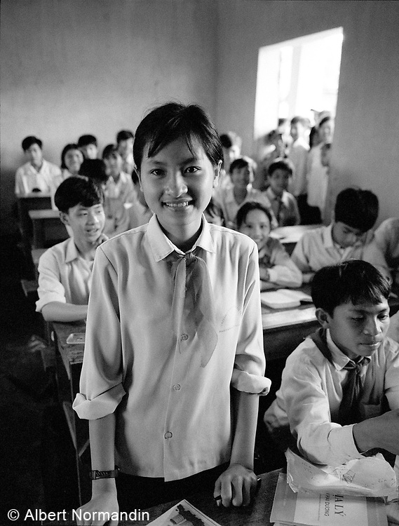 Young student standing and smiling in classroom