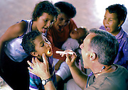 Doctor examines family who all open mouths at the same time in clinic in Tegucigalpa, Honduras, after Hurricane Mitch.