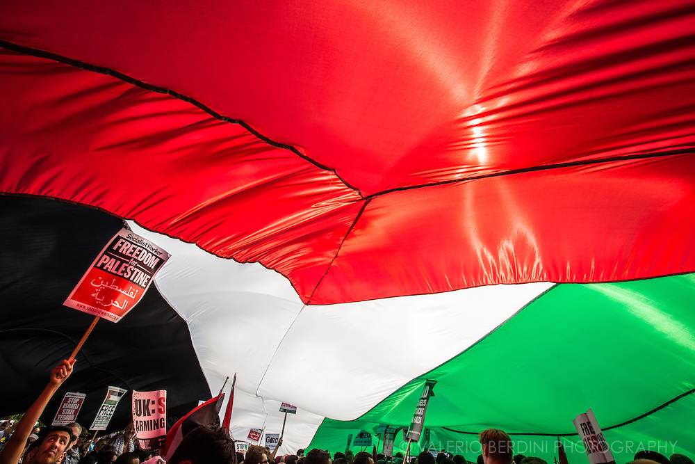 Hundreds of people gather under a huge Palestinian flag. Stop the massacre in Gaza. 150.000 thousands people march in the streets of Central London to Hyde Park ask the end of Israeli invasion of Gaza. 9 August 2014