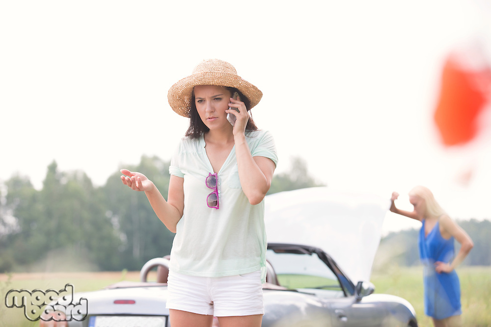 Worried woman using cell phone while friend examining broken down car outdoors