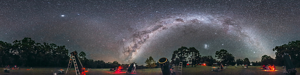 A 360&deg; panorama of the southern hemisphere autumn sky over the observing field at the 2017 OzSky Star Party, at the Warrumbungles Mountain Motel, near Coonabarabran, NSW, Australia. The entire southern Milky Way arches overhead, from Scorpius and Sagittarius rising at left, to Carina and Crux high in the south at centre, to Canis Major and Puppis setting at right. <br /> <br /> The Large Magellanic Cloud is at right of centre. The formation of the Dark Emu in dark dust lanes in the Milky Way is at centre, rising. Some red bands of airglow discolour the sky. <br /> <br /> Jupiter is the bright object at left, with the Gegenschein glow at the anti-solar point between Jupiter and the Milky Way. The faint Zodiacal Band can be seen arching across the sky at left, in the northern sky. The Milky Way dominates the southern sky. The South Celestial Pole is above the tree at right of centre. <br /> <br /> The telescopes on the field are mostly large Dobsonian reflectors in the 18- to 30-inch class, for use of the star party participants. <br /> <br /> This is a stitch of 8 segments, each 30 seconds at f/2.5 with the Rokinon 14mm lens, in portrait orientation, and with the Canon 6D at ISO 6400. Stitched with PTGui in equirectangular projection.