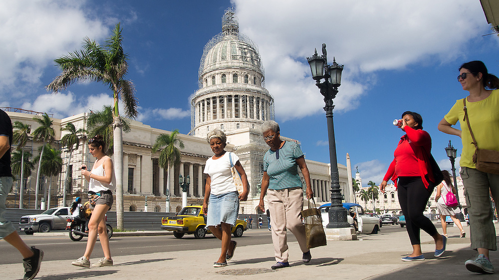 Locals and tourists walk by El Capitolio, or National Capitol Building in Havana, Cuba, which was the seat of government in Cuba until after the Cuban Revolution in 1959, and is now home to the Cuban Academy of Sciences. Travel images from Havana Cuba. Pictures by Chris Pavlich Photography.