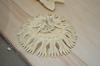 sardinian bread sculpture before cooking: on a small round decorated like nest shape is a little family of four birds.