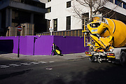 Against a purple construction site hoarding, passer-by and cement mixer in incongruous city landscape.
