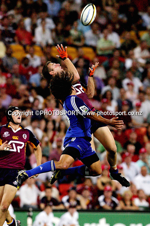 Reds fullback Chris Latham leaps high to beat Isa Nacewa to a midfield bomb during the 2006 Super 14 rugby union match between the Reds and the Auckland Blues at Suncorp Stadium, Brisbane, Australia, on Saturday 25 February, 2006. The Blues defeated the Reds 21-20. Photo: PHOTOSPORT<br />