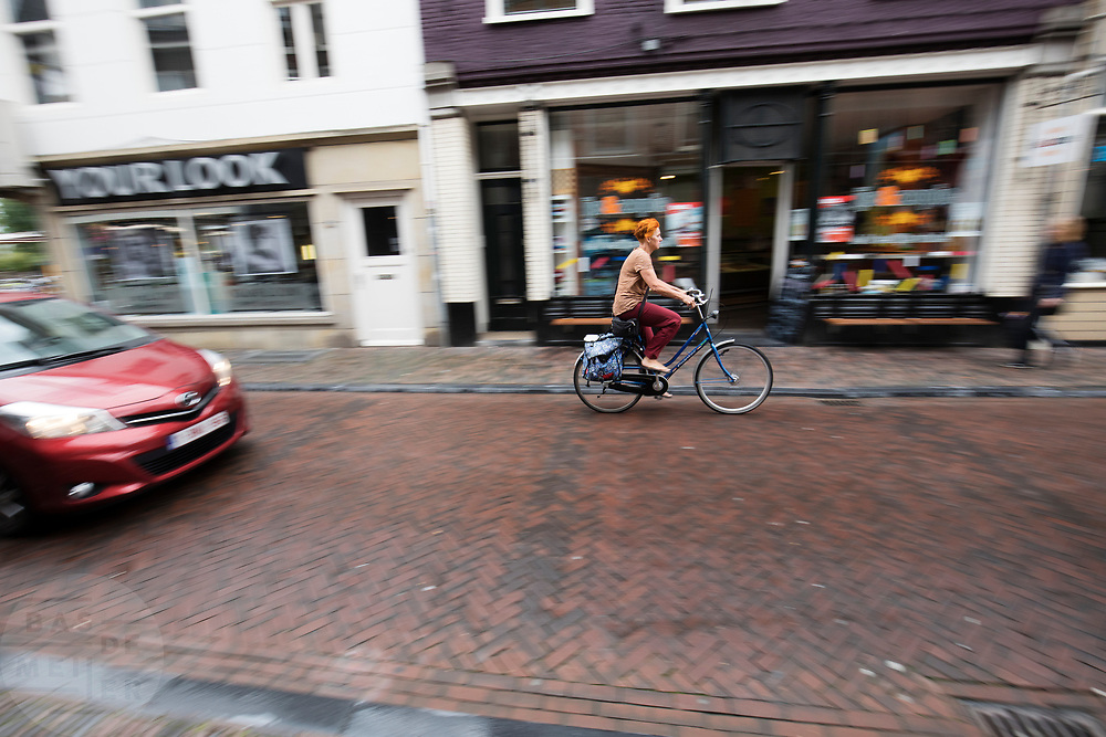 In Utrecht rijdt een vrouw op een fiets door de Twijstraat met achter haar een auto.<br /> <br /> In Utrecht a woman cycles at the Twijnstraat, with a car behind her.